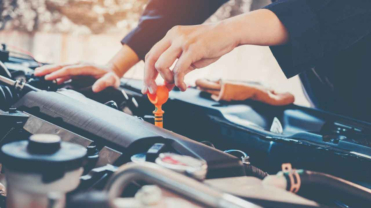 checking engine oil level by removing dipstick